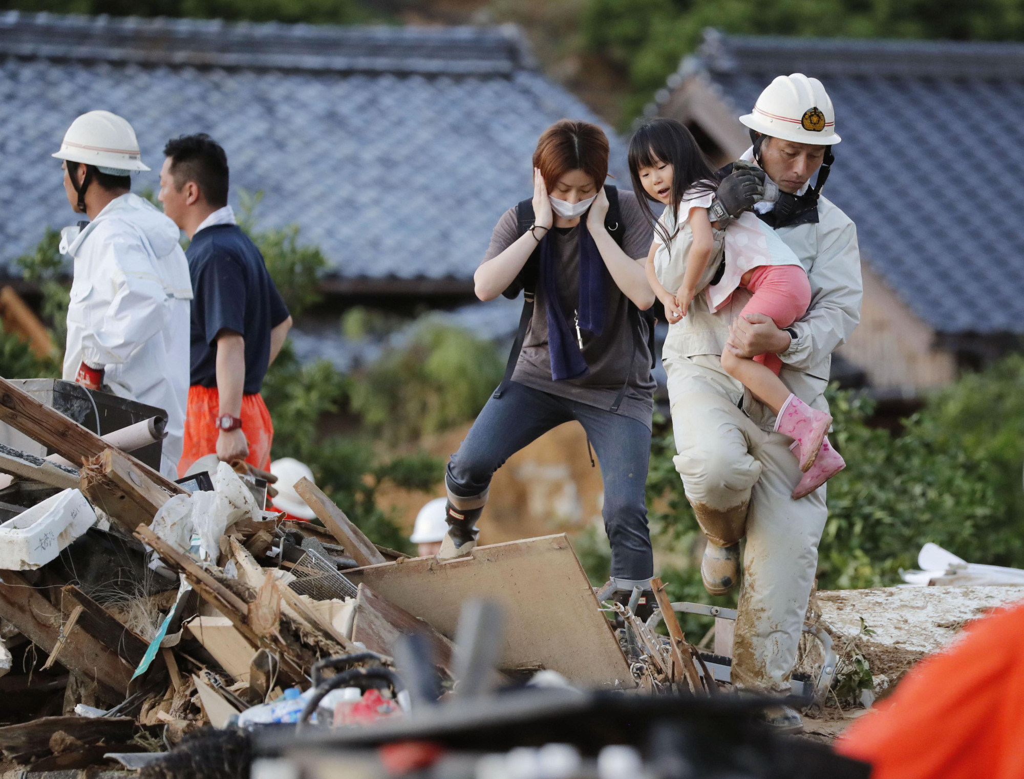 Picking up the pieces: A rescue worker walks on rubble in Uwajima, Ehime Prefecture, on July 8 while holding a girl in his arms. | KYODO