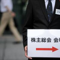 An attendant holds a sign for a shareholder meeting in Tokyo in June 2015. | BLOOMBERG
