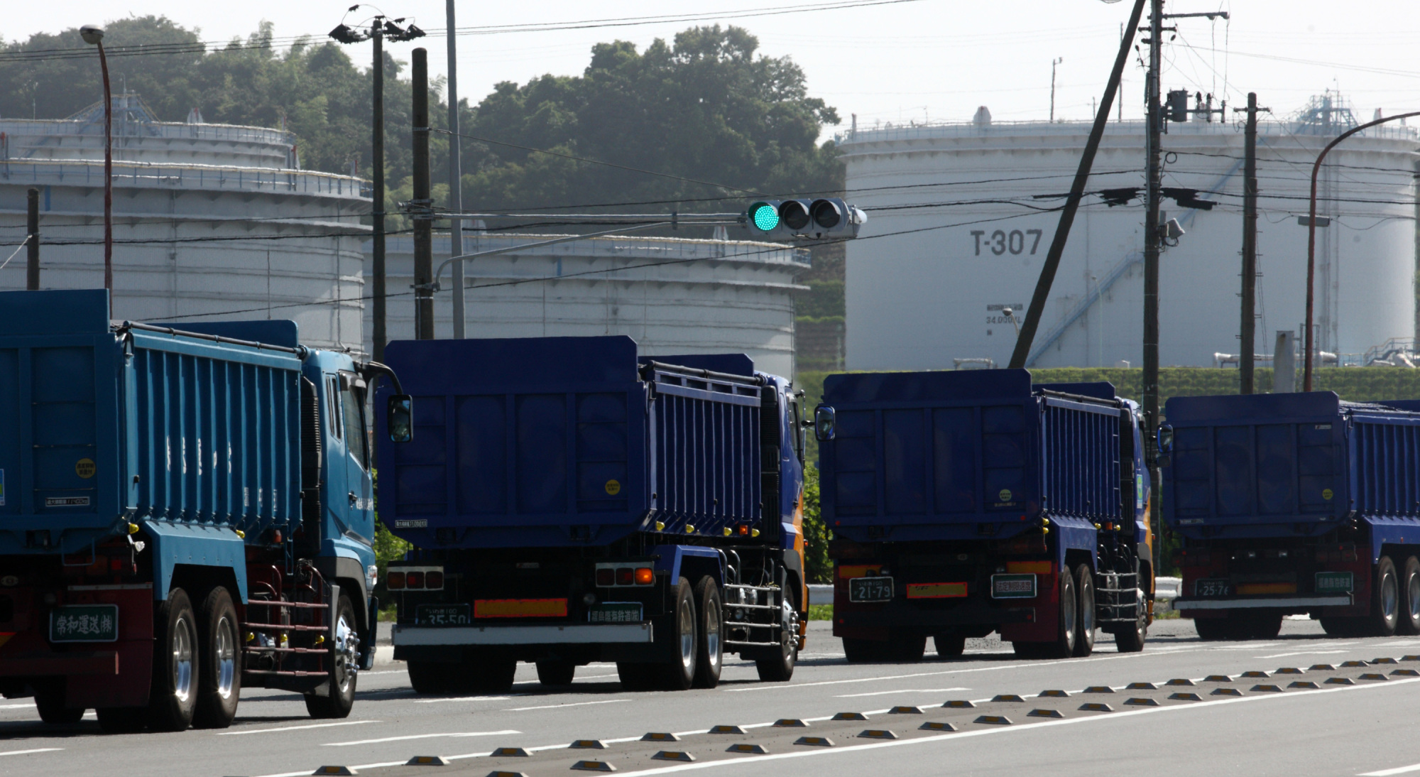 Trucks carrying coal roll past an oil terminal at Onahama port in the city of Iwaki, Fukushima Prefecture. | BLOOMBERG