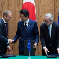 Prime Minister Shinzo Abe shakes hands with European Council President Donald Tusk as European Commission President Jean-Claude Juncker looks on after the signing of a Japan-EU trade deal in Tokyo on Tuesday. | AFP-JIJI