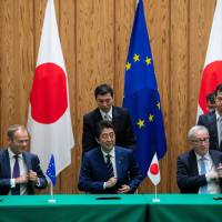 Prime Minister Shinzo Abe,  European Council President Donald Tusk (left) and European Commission President Jean-Claude Juncker reach for their pens at a July 17 signing ceremony for a trade deal that will eliminate almost all tariffs between Japan and the EU. | BLOOMBERG