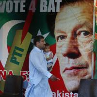 A man walks past a poster of Imran Khan, head of Pakistan Tehreek-e-Insaf party, at a market in Islamabad on Saturday. The former cricket star's party says it has acquired the support of the lawmakers required to form a coalition government. | AP