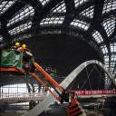 Workers stand on a boom lift inside a terminal under construction at Beijing's new international airport July 6, 2018. The new airport is scheduled to begin operations next year.