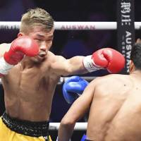 Sho Kimura punches challenger Froilan Saludar in the first round of Friday's WBO flyweight title fight in Qingdao, China. Kimura retained his title with a sixth-round knockout. | KYODO