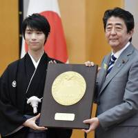 Yuzuru Hanyu receives the People's Honor Award from Prime Minister Shinzo Abe during a ceremony on Monday morning in Tokyo. | KYODO