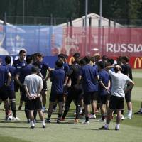 Samurai Blue coach Akira Nishino (second from left) speaks to his players during a training session on Saturday in Kazan, Russia. | AP