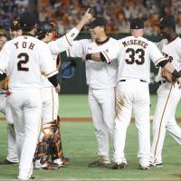 Teammates celebrate with Giants pitcher Shun Yamaguchi (center) after he completed his no-hitter on Friday night. | KYODO