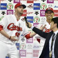 Carp pitcher Kris Johnson sings 'Happy Birthday' to teammate Kosuke Tanaka during their hero interview after Hiroshima's win over Tokyo Yakult on Wednesday. | KYODO