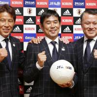 Hajime Moriyasu (center) poses for photos with former JFA technical director Akira Nishino (left) and JFA president Kozo Tashima after being named manager for Japan's 2020 Olympic men's team on Oct. 30, 2017. Moriyasu is thought to be the leading candidate to succeed Nishino as manager of the full national team. | KYODO