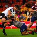 The Sunwolves' Kazuki Himeno is tackled by the Reds' Alex Mafi in Super Rugby action on Friday night in Brisbane, Australia.