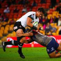 The Sunwolves' Kazuki Himeno is tackled by the Reds' Alex Mafi in Super Rugby action on Friday night in Brisbane, Australia. | AFP-JIJI
