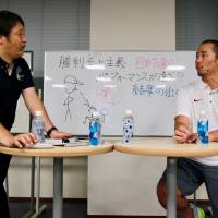 Nippon Sport Science professor Masamitsu Ito (left) and Stanford football assistant coach Tsuyoshi Kawata discuss some of the issues that arise in  coaching in both Japan and the United States during a workshop on Friday in Tokyo. | KAZ NAGATSUKA