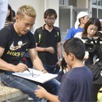 Japan national team and Galatasaray defender Yuto Nagatomo signs autographs on July 18 during an event at a school in Ozu, Ehime Prefecture,  a city near his hometown Saijo that was hit hard by deadly torrential rains. | KYODO