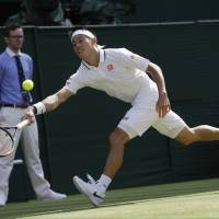 Kei Nishikori of Japan returns the ball to Novak Djokovic of Serbia during their men's quarterfinal match at the Wimbledon Tennis Championships in London Wednesday. | AP