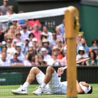 Japan's Kei Nishikori falls to the floor while playing Serbia's Novak Djokovic during their men's singles quarter-finals match on the ninth day of the 2018 Wimbledon Championships at The All England Lawn Tennis Club in Wimbledon, southwest London, on Wednesday. | AFP-JIJI