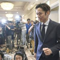 Daisuke Takahashi walks past reporters at a news conference to announce his return to competitive figure skating on Sunday. | KYODO