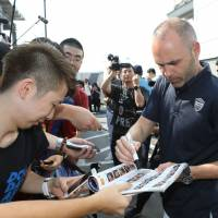 Andres Iniesta signs autographs after arriving at Kansai International Airport on Wednesday. | AFP-JIJI