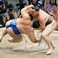 Hakuho outmuscles Kotoshogiku on Tuesday at the Nagoya Sumo Tournament. | KYODO