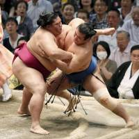 Sekiwake Mitakeumi (left) forces No. 2 maegashira Chiyonokuni out of the ring during their bout on the eighth day of the Nagoya Grand Sumo Tournament on Sunday. | KYODO