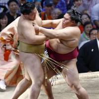 Mitakeumi (right) forces Kagayaki out of the raised ring on Tuesday at the Nagoya Grand Sumo Tournament. | KYODO