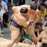Asanoyama (left) grapples with Nishikigi during 11th day of the Nagoya Basho. Asanoyama  defeated the No. 10 maegashira to earn his ninth victory at the tournament. | KYODO