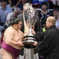 Mitakeumi (left) accepts the Emperor's Cup from JSA president Hakkaku on the final day of the Nagoya Grand Sumo Tournament on Sunday. | KYODO