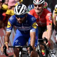 Fernando Gaviria (left) pedals ahead of Andre Greipel after crossing the finish line to win Stage 4 of the Tour de France on Tuesday in Sarzeau, France. | AFP-JIJI