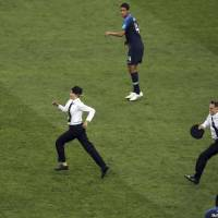 France's Raphael Varane (top) and France's Samuel Umtiti look at two people who invaded the pitch during the final match between France and Croatia at the 2018 soccer World Cup in Luzhniki Stadium in Moscow Sunday. | AP