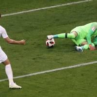 Croatia goalkeeper Danijel Subasic makes a save in front of England's Harry Kane during the semifinal match between Croatia and England at the 2018 soccer World Cup in the Luzhniki Stadium in Moscow Wednesday8. | AP