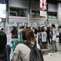 People watch a TV screen at New Chitose Airport in Hokkaido in October 2016. | KYODO