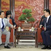 Finance Minister Taro Aso (left) meets with Chinese vice premier, Han Zheng, in Beijing on Thursday. | POOL / VIA KYODO