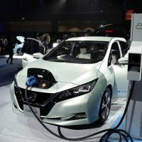 A new Leaf electric vehicle is connected to a charging station at its unveiling by Nissan Motor Co. in the city of Chiba in September 2017. Renault-Nissan-Mitsubishi and other carmakers have all channeled funds into battery companies. | BLOOMBERG