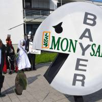 A protester wears a pill-shaped costume bearing the names of Bayer and Monsanto during a demonstration against the takeover of U.S. seeds and pesticides maker Monsanto by German chemicals firm Bayer outside the World Conference Center, where the annual general meeting of chemicals giant Bayer took place in Bonn, western Germany, in May. A cancer victim's surprise court victory over U.S. pesticide maker Monsanto could open the floodgates to a slew of similar lawsuits, potentially leaving the firm's new German owner Bayer with a major case of buyer's remorse. | AFP-JIJI