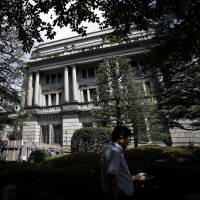 A man walks past the Bank of Japan headquarters in Tokyo. | BLOOMBERG
