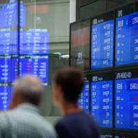 Visitors look at screens displaying stock indices at the Tokyo Stock Exchange in July. | BLOOMBERG