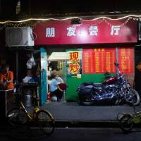 This picture taken Sunday shows a Harley-Davidson motorcycle parked in front of a restaurant in Shanghai. From Harley-Davidson motorcycles and American bourbon to Chinese parts and machinery, the world's two largest economies have exchanged punitive tariffs that slice through a wide swath of products. | JOHANNES EISELE / VIA AFP-JIJI