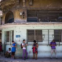 Pedestrians use their smartphones to surf the internet in Havana Wednesday. The state telecommunications company of Cuba launched on Wednesday the latest, and most extensive, of a recent series of test runs of a mobile network that would give ordinary citizens greater access to the internet than has existed before on the island. | AP