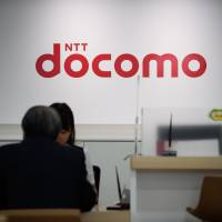 An employee briefs a customer at an NTT Docomo Inc. store in Tokyo. The mobile phone carrier plans to review its two-year smartphone contracts by next March, after rival KDDI Corp. pledged to change its contracts in response to government warnings. | BLOOMBERG