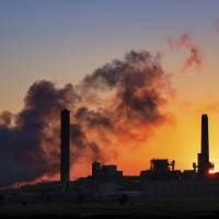 The Dave Johnson coal-fired power plant is silhouetted against the morning sun in Glenrock, Wyoming, in July. The Trump administration on Tuesday proposed a major rollback of Obama-era regulations on coal-fired power plants, striking at one of the former administration's legacy programs to rein in climate-changing fossil-fuel emissions. | J. DAVID AKE / VIA AP