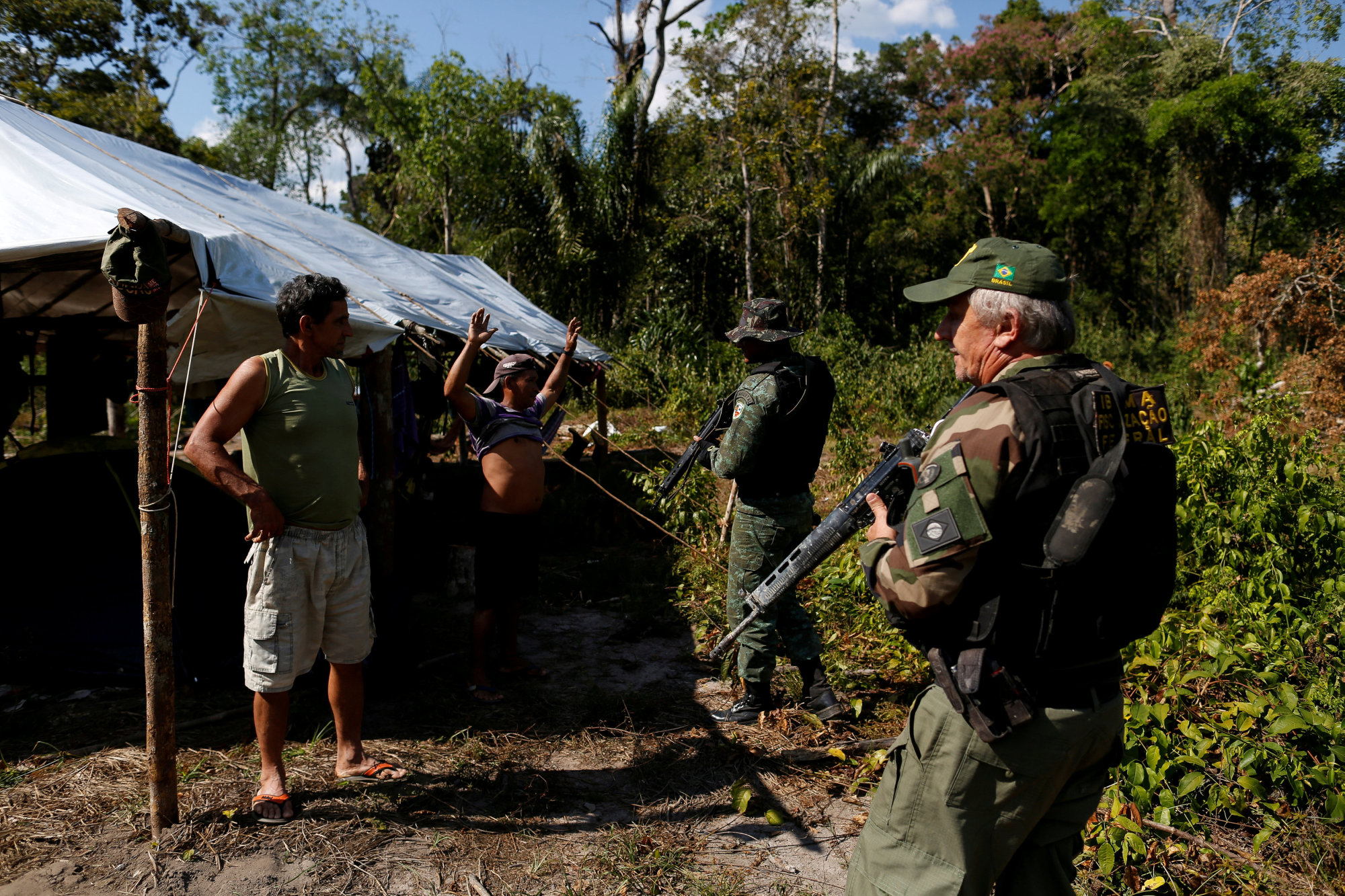 Agents of the Brazilian Institute for the Environment and Renewable Natural Resources, or Ibama, check a man at an illegal logging camp during 'Operation Green Wave' to combat illegal logging in Apui, in the southern region of the state of Amazonas, Brazil, July 28. | REUTERS