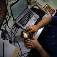 Heroz Inc.'s 'Shogi Wars' game is displayed on a smartphone at the company's headquarters in Tokyo in June. | BLOOMBERG