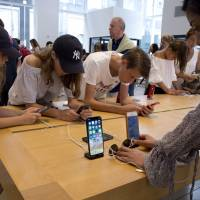 Customers browse products in an Apple store in New York on Aug. 2. Apple Inc. is planning to unveil three new phones in September, sources said. | AP