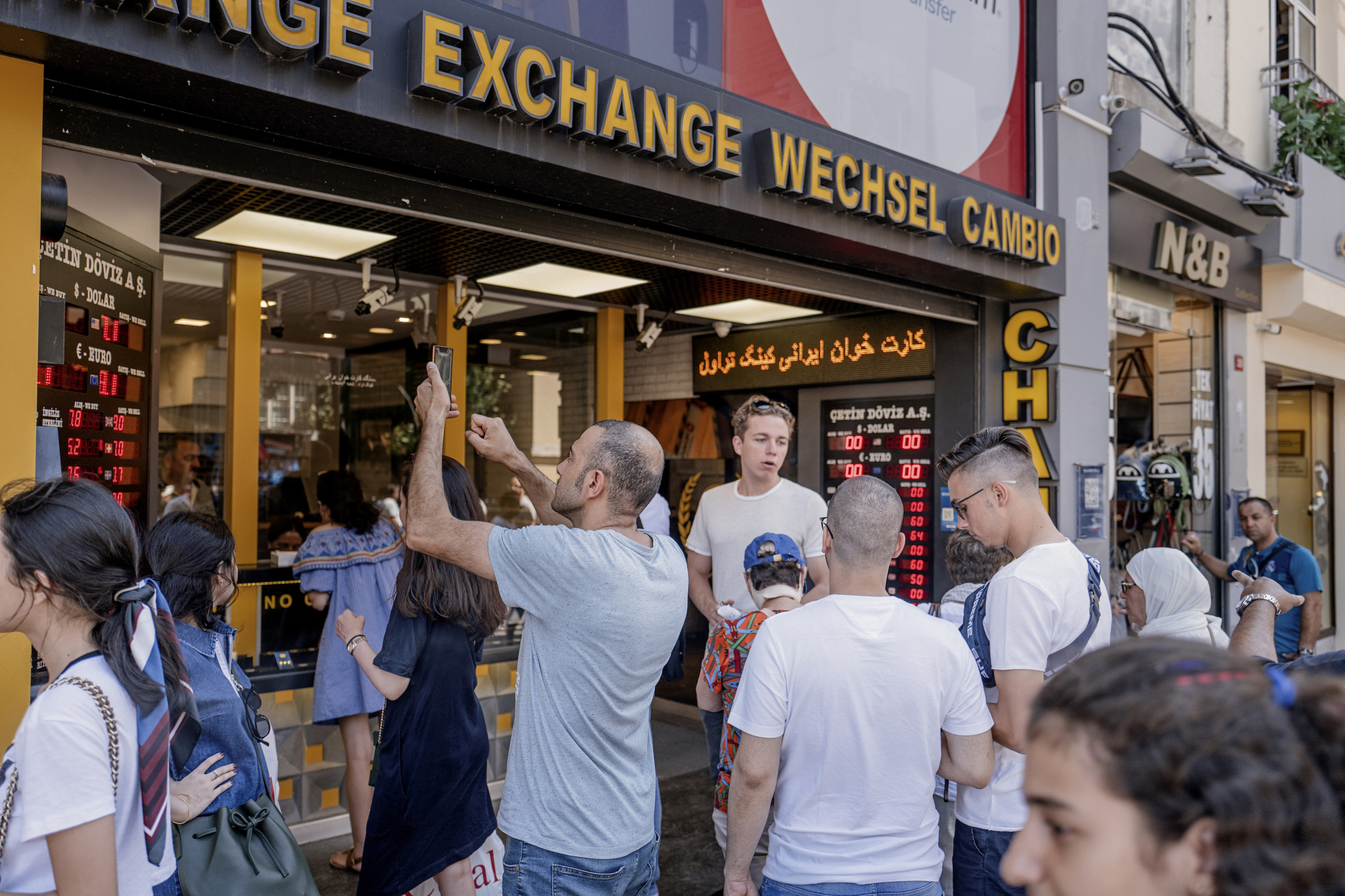 A tourist takes a photograph of the latest foreign currency rates posted outside an exchange bureau in Istanbul on Monday. | BLOOMBERG