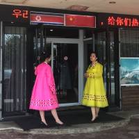 Two waitresses dressed in traditional Korean costumes are seen in front of a North Korean cuisine restaurant in Dandong, Liaoning province, China, Monday. | REUTERS