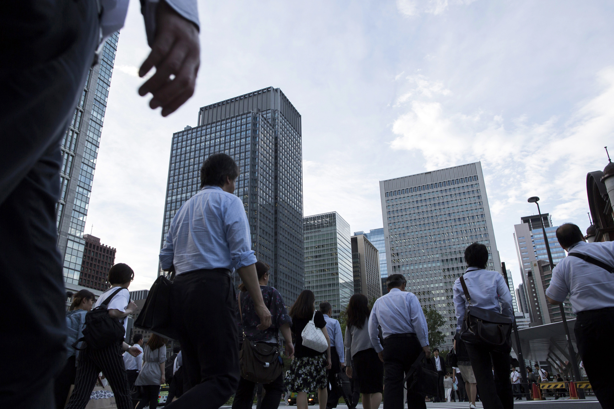 Commuters cross a road in the central business district of Tokyo on June 27. A poll shows most big and midsized Japanese firms favor a more open immigration system to offset the country's labor shortage. | BLOOMBERG