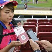 This handout photo provided by Rakuten shows how someone can use a smartphone and QR codes to buy refreshments. | KYODO