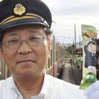 Choshi Electric Railway President Katsunori Takemoto shows off a snack called the Mazui Bo, or 'foul-tasting stick,' in an effort to shore up the struggling railway's bottom line. | CHOSHI ELECTRIC RAILWAY / VIA KYODO