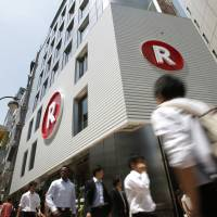 Pedestrians walk past a cafe operated by Rakuten Inc. in Tokyo. The e-commerce giant has an ambitious plan to build a cutting-edge wireless network to take on existing phone operators. | BLOOMBERG