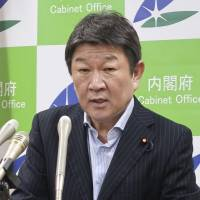 Toshimitsu Motegi, minister in charge of economic and fiscal policy, speaks at a news conference in Tokyo on Friday after submitting an annual white paper on the economy. | KYODO