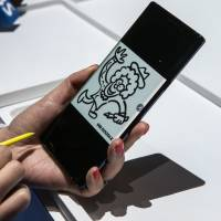 An attendee demonstrates a Samsung Electronics Co. Galaxy Note 9 S-Pen stylus on a Galaxy Note 9 smartphone during the Samsung Unpacked product launch event in New York on Thursday. | BLOOMBERG